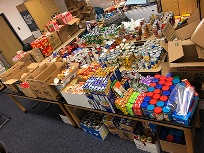 Photo showing a room full of tables filled with donated food items