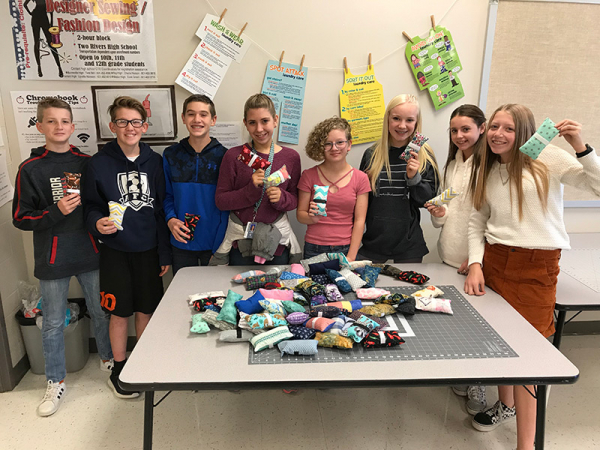 Students surround table filled with seat belt covers they made.